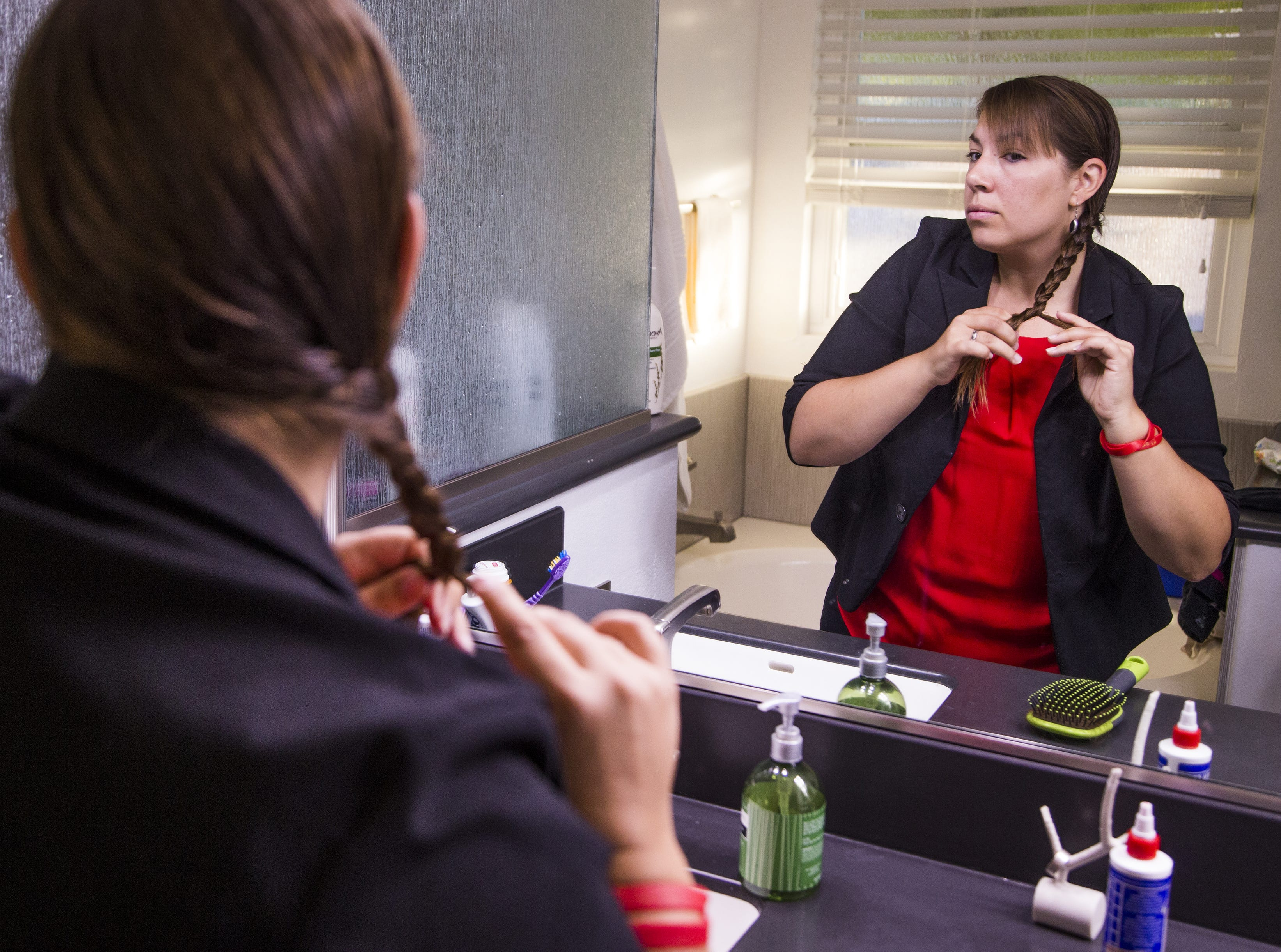 Rebecca Garelli brushes her hair at 6:41 am before heading out for her 30-mile commute to Sevilla West Elementary School in Phoenix, Monday, September 17, 2018. Garelli has been one of the leaders of the #RedforEd movement, demanding increased funding for education in Arizona.