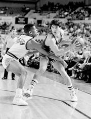 Jazz guard John Stockton looks for an open teammate while Suns guard Kevin Johnson reaches inside for a steal in 1989.