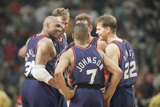 Suns players Charles Barkley (left), Kevin Johnson, and Danny Ainge are all smiles as they confer late in the triple-overtime period of their 129-121 win over the Chicago Bulls on June 13, 1993, in Chicago. Also in on the celebration are Tom Chambers, rear left, and Dan Majerle.