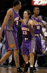 Steve Nash high-fives teammates Shawn Marion (31) and Raja Bell (19) in 2005.