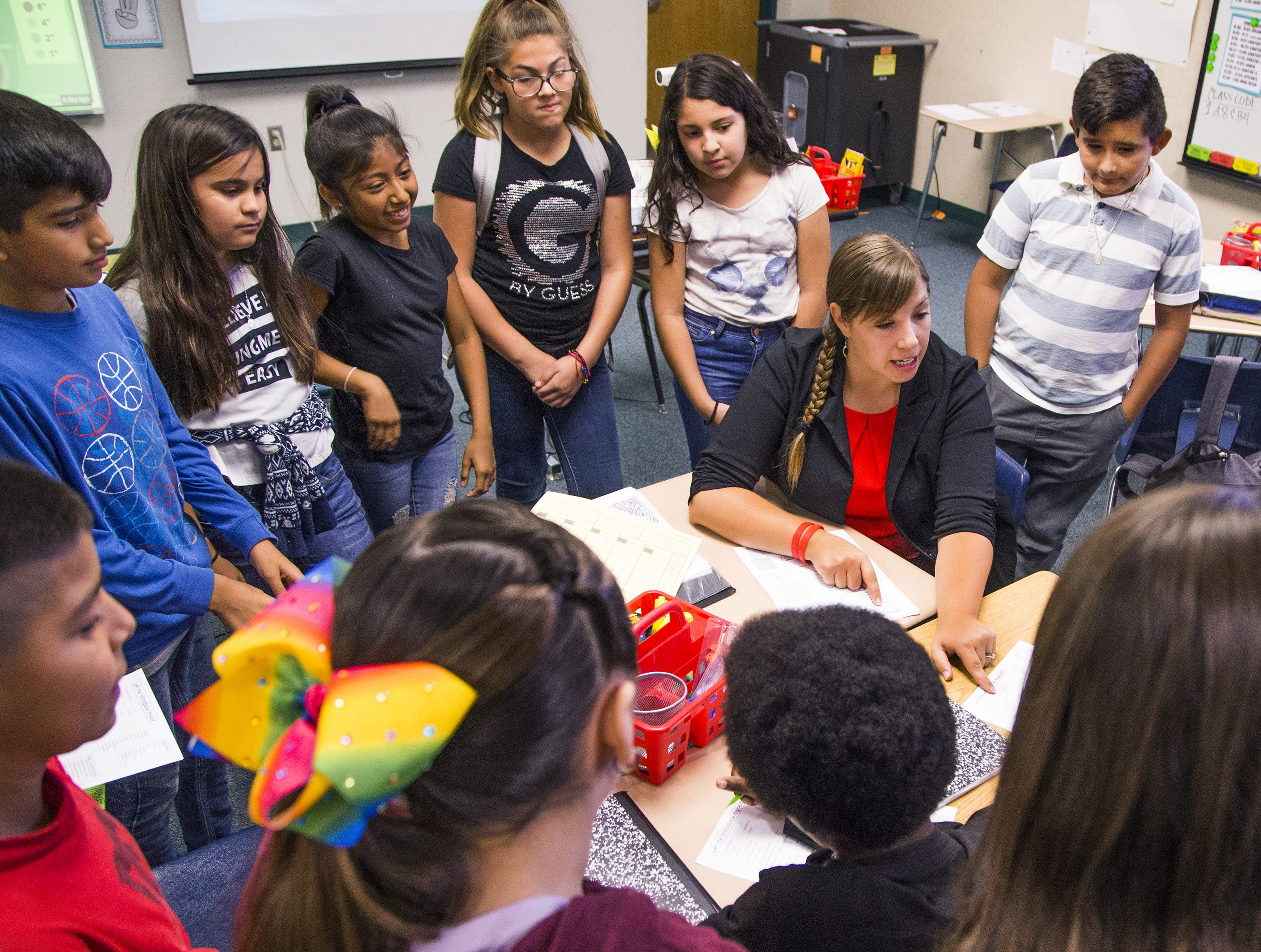 Rebecca Garelli , sitting, helps her 6th grade class at Sevilla West Elementary School in Phoenix, at 10:45 am, Monday, September 17, 2018. Garelli has been one of the leaders of the #RedforEd movement, demanding increased funding for education in Arizona.