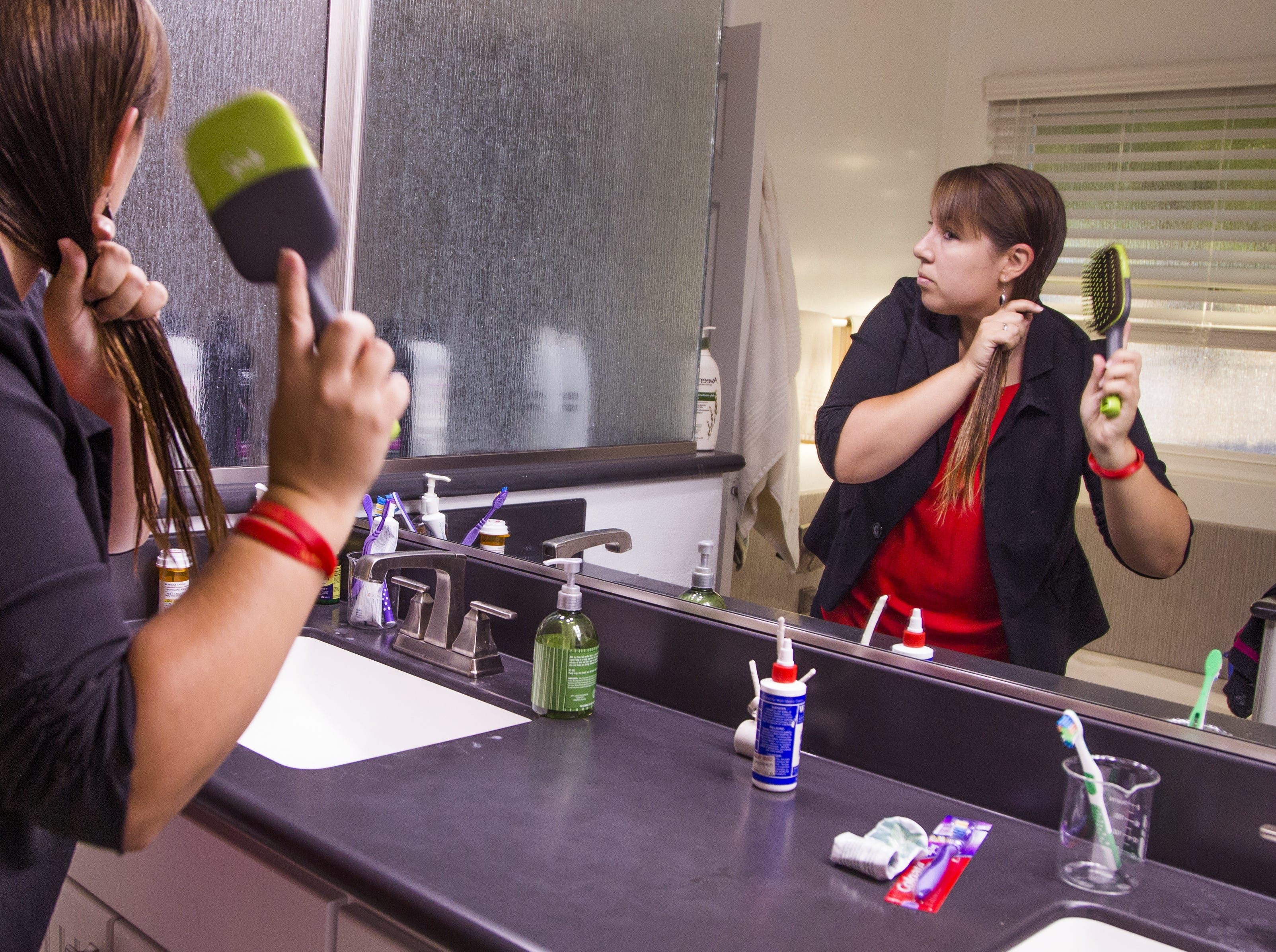 Rebecca Garelli brushes her hair at 6:40 am before heading out for her 30-mile commute to Sevilla West Elementary School in Phoenix, Monday, September 17, 2018. Garelli has been one of the leaders of the #RedforEd movement, demanding increased funding for education in Arizona.