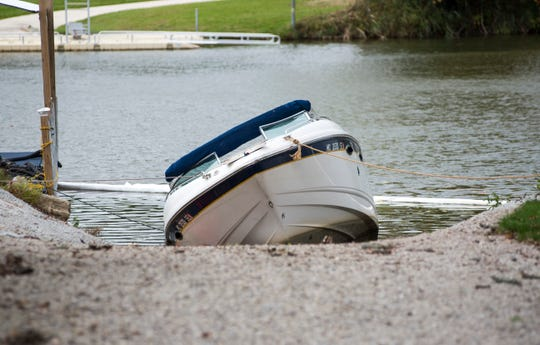 Port Huron Township firefighters deployed containment booms to control a fuel spill from a boat that sunk in the Black River Thursday.