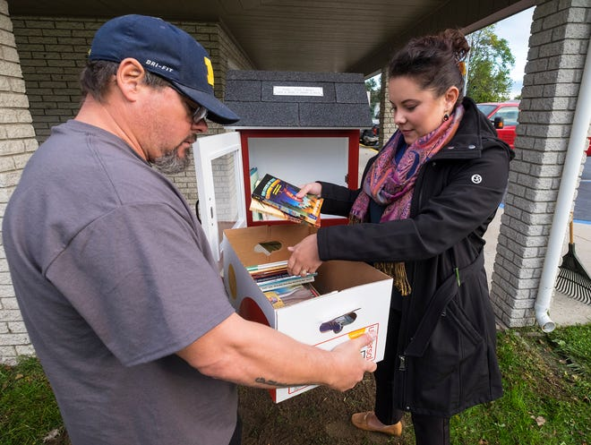 Port Huron Housing Commission maintenance employee Ron Gurnsey, left, holds a box full of books for administrative assistant Callie Oppertshauser while she fills a free library Thursday, Oct. 11, 2018 at Gratiot Village in Port Huron. For the Port Huron Housing Commission's 50th anniversary, its staff has built free libraries that will be installed at each of its family apartments in Port Huron.