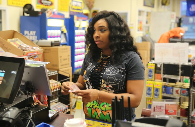 Watisha McKinney buys a Mega Millions ticket at the Thrifty Beverage on North Hamilton in the City of Poughkeepsie on Thursday. She works at the adjoining Western Union and said she decided to buy a ticket on a whim.