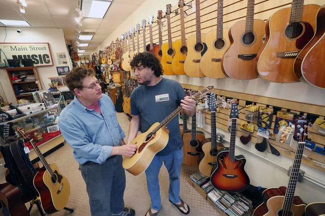 From left, David Bernz and his son Jake look over a guitar on the rack at Jake's Main Street Music in Beacon Oct. 10, 2018. They have been in business for five years and together with the Towne Crier are planning a free music event on Sunday Oct. 14th at the Towne Crier.