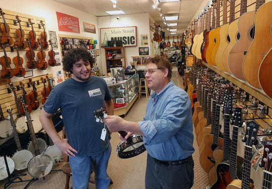 From right, David Bernz and his son Jake look over a banjo on the rack at Jake's Main Street Music in Beacon Oct. 10, 2018. They have been in business for five years and together with the Towne Crier are planning a free music event on Sunday Oct. 14th at the Towne Crier.