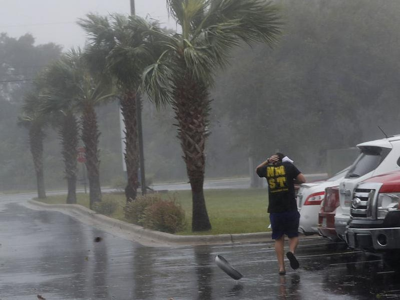 A hubcap blows by as a man runs to his car during Hurricane Michael in Panama City, Fla., Wednesday, Oct. 10, 2018. (AP Photo/Gerald Herbert)