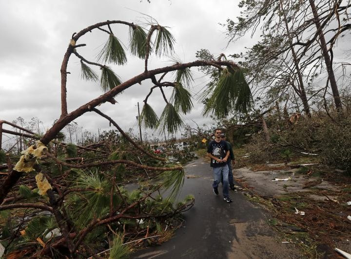 People walk through downed trees in a heavily damaged neighborhood in the aftermath of Hurricane Michael in Panama City, Fla., Wednesday, Oct. 10, 2018. Supercharged by abnormally warm waters in the Gulf of Mexico, Hurricane Michael slammed into the Florida Panhandle with terrifying winds of 155 mph Wednesday, splintering homes and submerging neighborhoods. (AP Photo/Gerald Herbert)