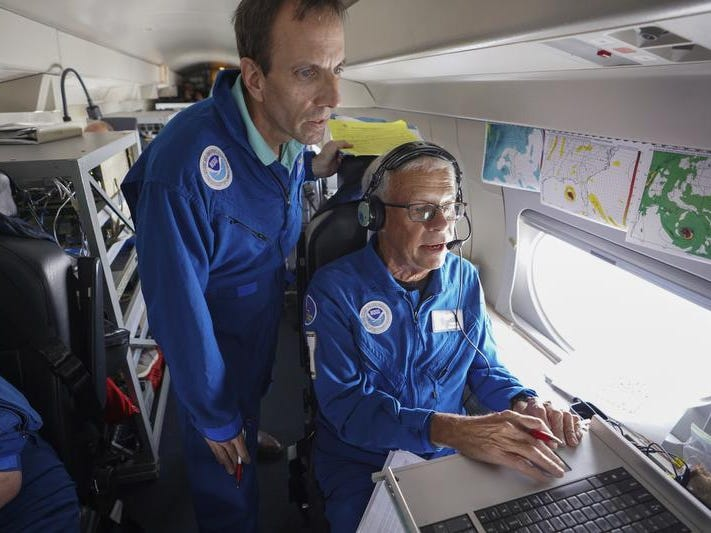Meteorologists John Kaplan and Jack Parrish view data streaming in on their workstation Wednesday, Oct. 10, 2018 aboard NOAA's Gulfstream IV jet callsign NOAA-49, a high-tech, high-flying, and high-speed platform used for hurricane forecasting and research. During this mission NOAA-49 flew a 2,400 mile 5.5 hour mission at 45,000 ft. around Hurricane Michael to create a detailed picture of the surrounding upper atmosphere. (Luis Santana/The Tampa Bay Times via AP)