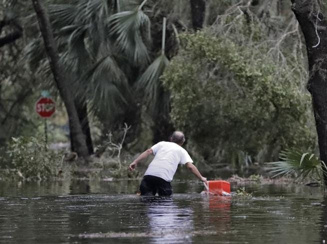 A resident of St. Marks, Fla., rescues a cooler out of the floodwaters near his home Wednesday, Oct. 10, 2018. Powerful Hurricane Michael slammed into the Florida Panhandle with terrifying winds of 155 mph Wednesday, splintering homes and submerging neighborhoods before continuing its destructive march inland across the Southeast. It was the most powerful hurricane to hit the continental U.S. in nearly 50 years and at least one death was reported during its passage. (AP Photo/Chris O'Meara)