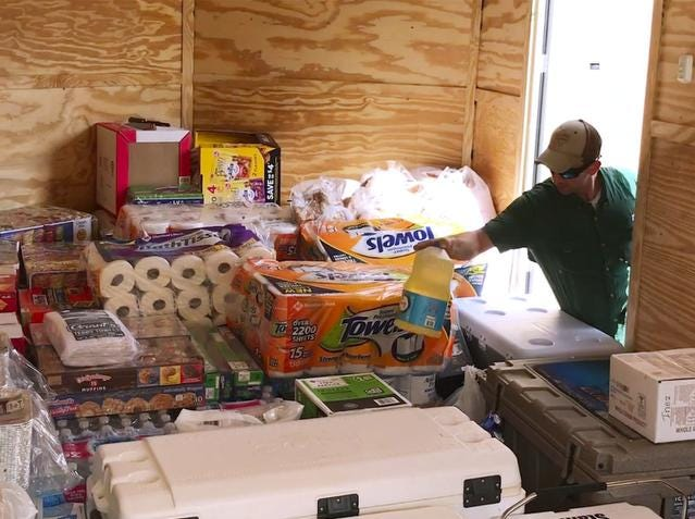 Ashton Flowers of Victoria, Texas, loads relief supplies in a trailer parked in Biloxi, Miss., on Wednesday, Oct. 10, 2018. Flowers was part of a group from Dalton Trucking, Inc., that is on their way to Florida to deliver relief supplies and food for victims of Hurricane Michael. (John Fitzhugh/The Sun Herald via AP)