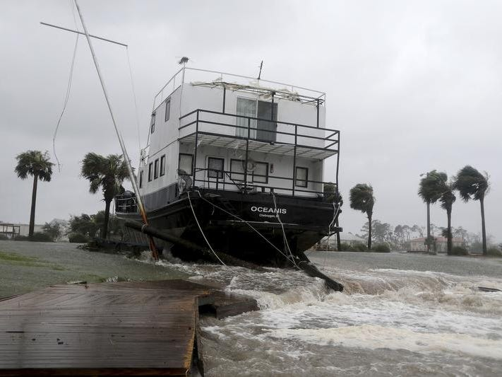 The Oceanis is grounded by a tidal surge at the Port St. Joe Marina, Wednesday, Oct. 10, 2018 in Port St. Joe, Fla. Supercharged by abnormally warm waters in the Gulf of Mexico, Hurricane Michael slammed into the Florida Panhandle with terrifying winds of 155 mph Wednesday, splintering homes and submerging neighborhoods. (Douglas R. Clifford/Tampa Bay Times via AP)