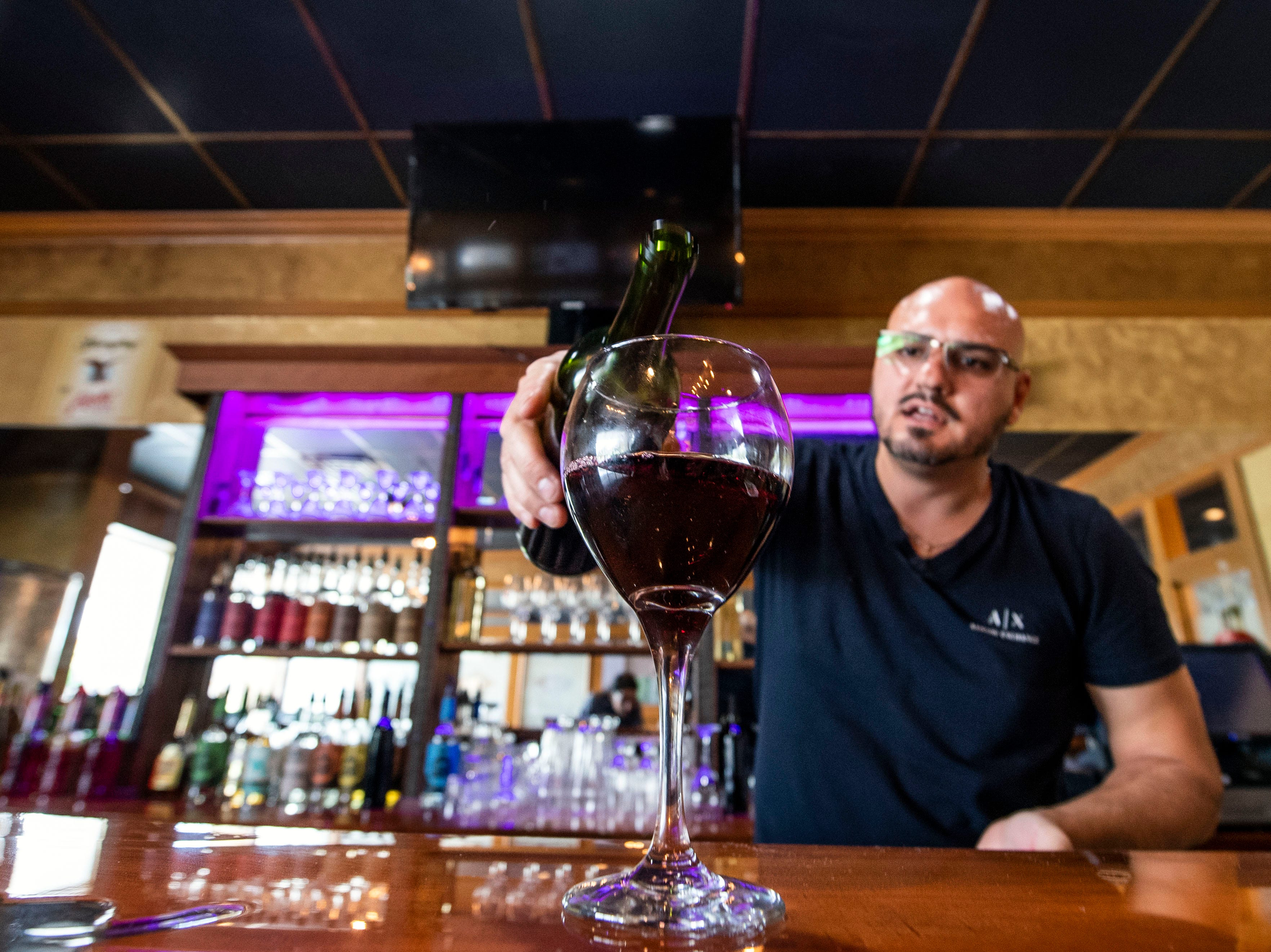 Vito Serradella pours a glass of Wood Fire Italian Grill's in-house wine, Wednesday, Oct. 10, 2018. The restaurant, which opened at the beginning of this year, has added on a bar, where they make their own wine to serve.