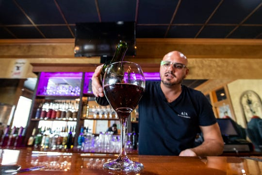 Vito Serradella pours a glass of Wood Fire Italian Grill's in-house wine, Wednesday, Oct. 10, 2018. The restaurant, which opened at the beginning of this year, has added on a bar, where they make their own wine.