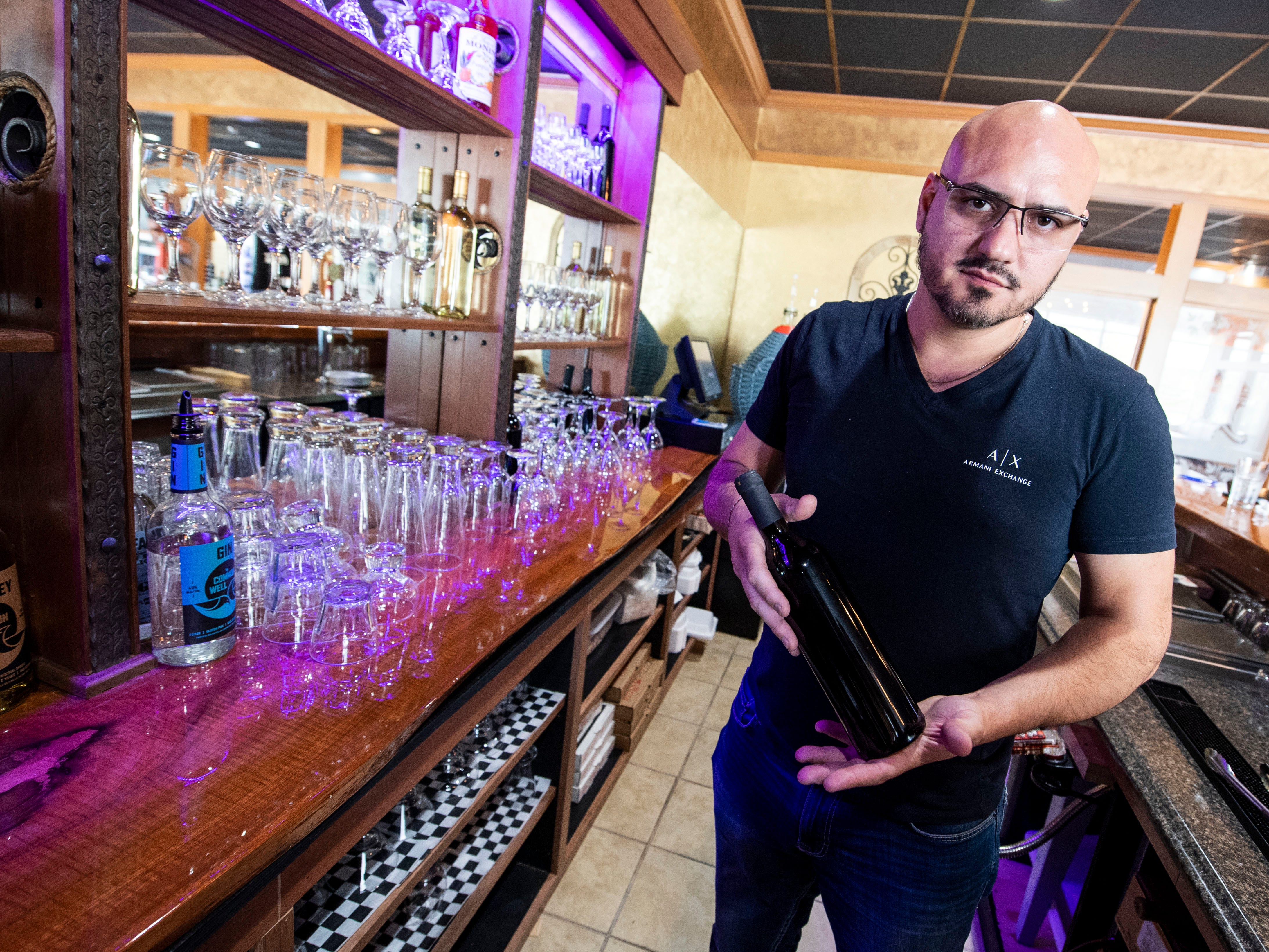 Vito Serradella, who co-owns Wood Fire Italian Grill, holds up a bottled of wine that was made in house, right beside the bar, Wednesday, Oct. 10, 2018. The restaurant, which opened at the beginning of this year, has added on a bar, where they make their own wine to serve.