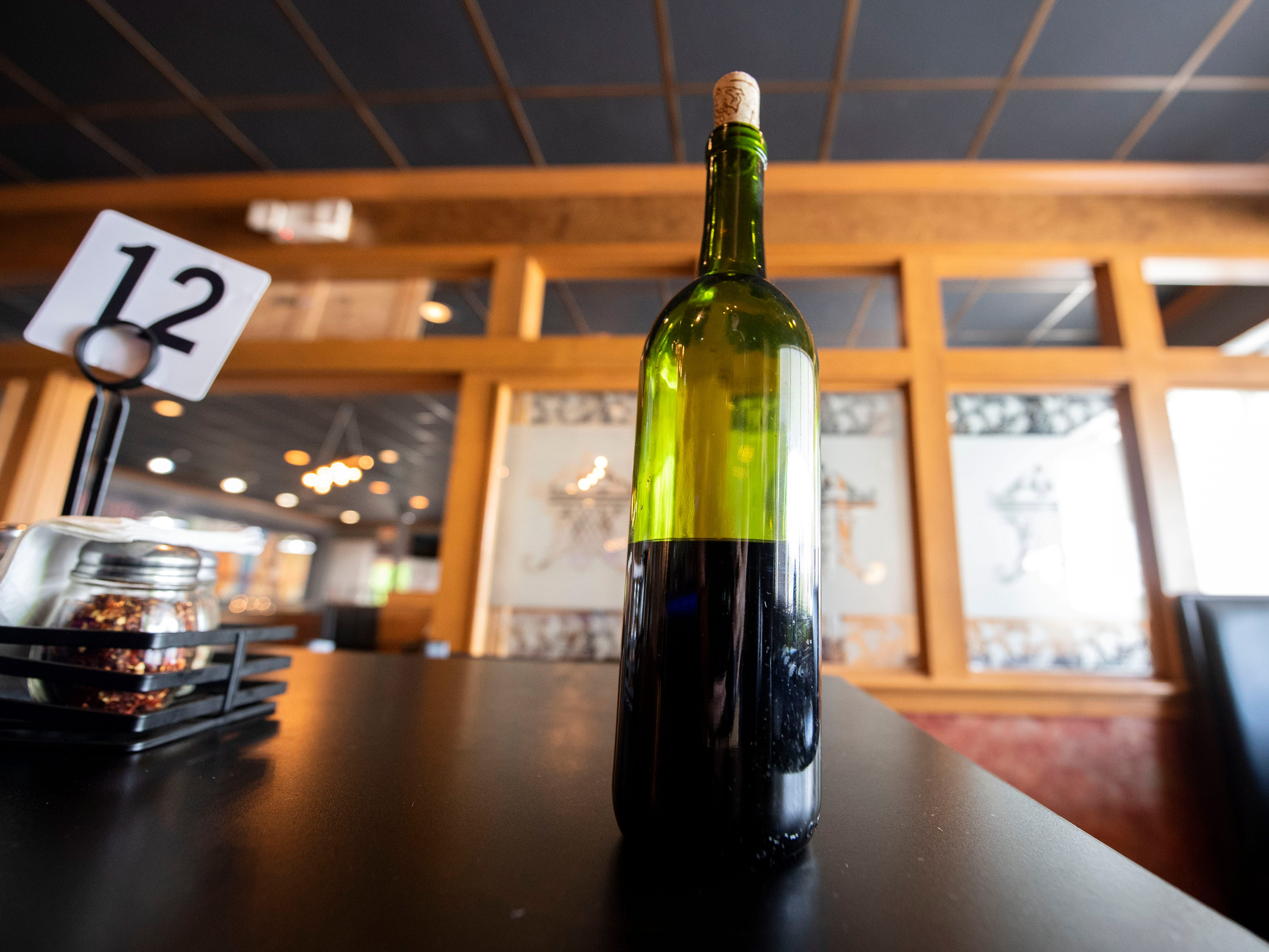 A bottle of Wood Fire Italian Grill's wine sits on a table in the new bar area, Wednesday, Oct. 10, 2018. The restaurant, which opened at the beginning of this year, has added on a bar, where they make their own wine to serve.