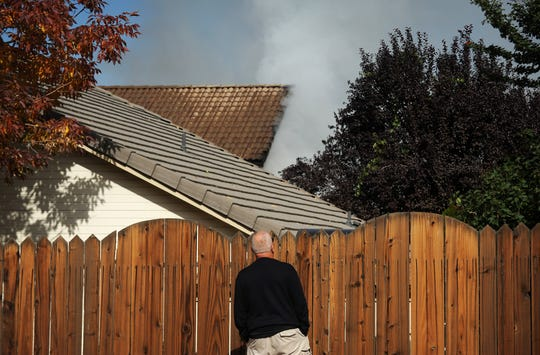 A neighbor stops to check out a house fire on the 900 block of Dolce Way, near the Northern Nevada Medical Center off Vista Boulevard in Sparks on Oct. 11, 2018.