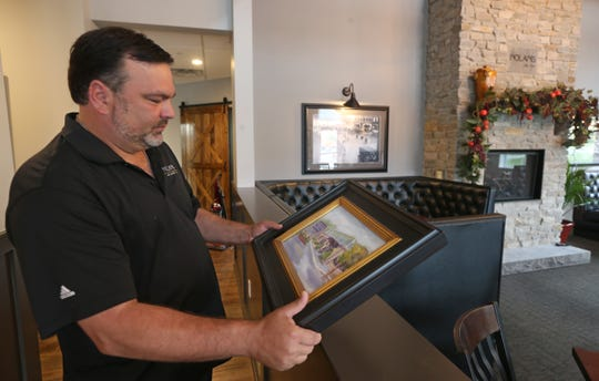Nick Violas looks over a painting that was given to him of the previous Nolan's building that was destroyed by a fire, while walking around his new Nolan's in Canandaigua.
