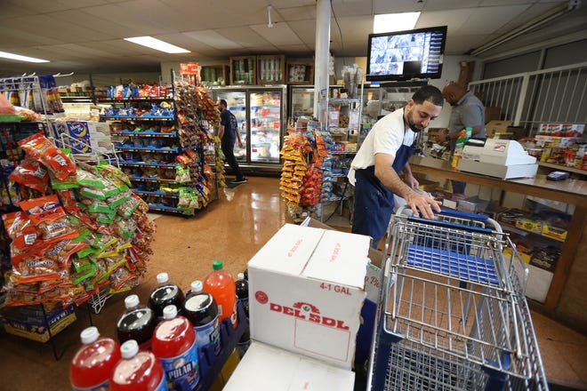 Sofyan Jaber, owner of Mr. Doug's Deli, rearranges the shopping carts at his grocery store.