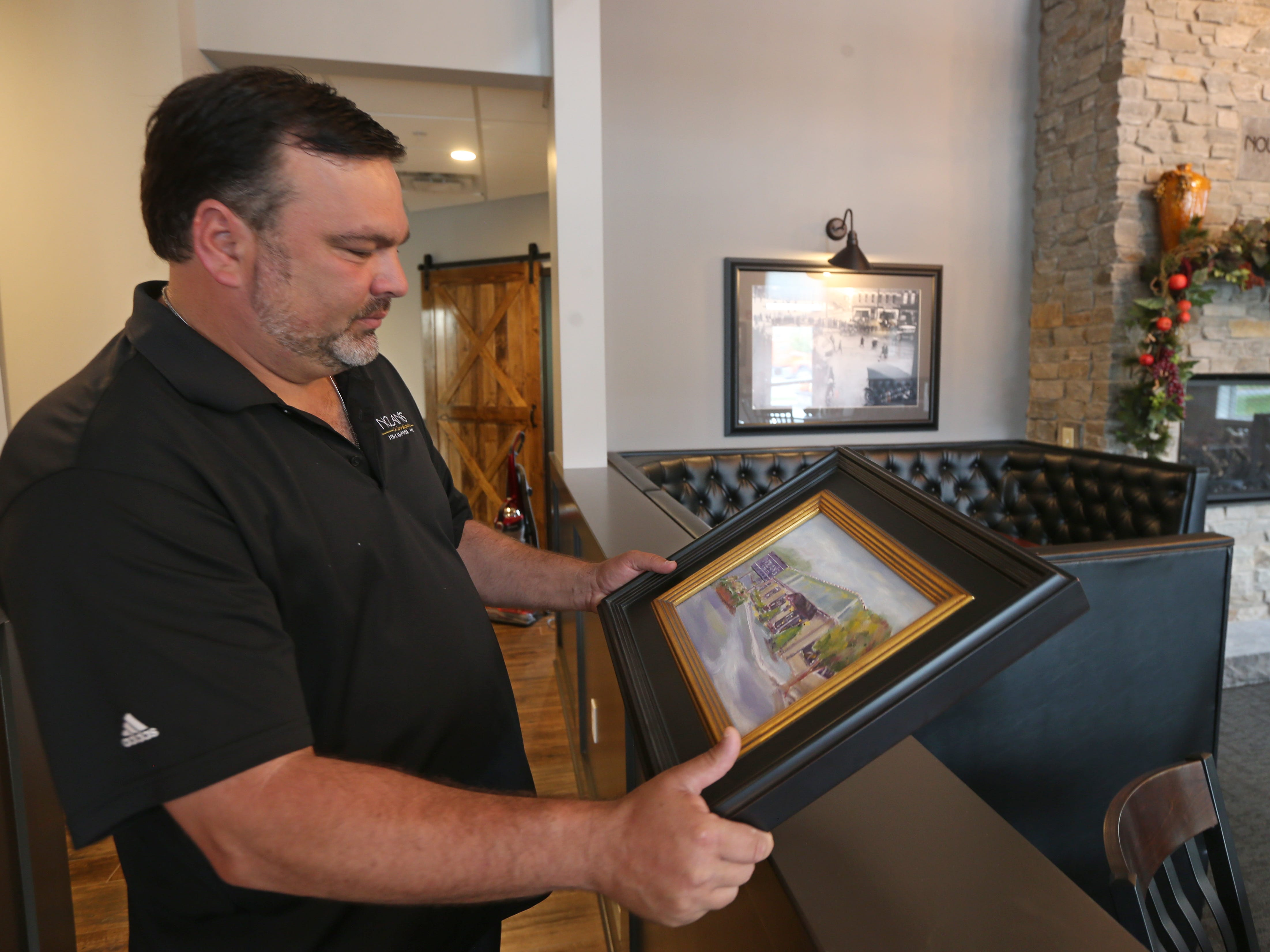 Nick Violas, owner of Nolan's, looks over a painting of the previous Nolan's building that was given to him, while walking around his new Nolan's in Canandaigua.