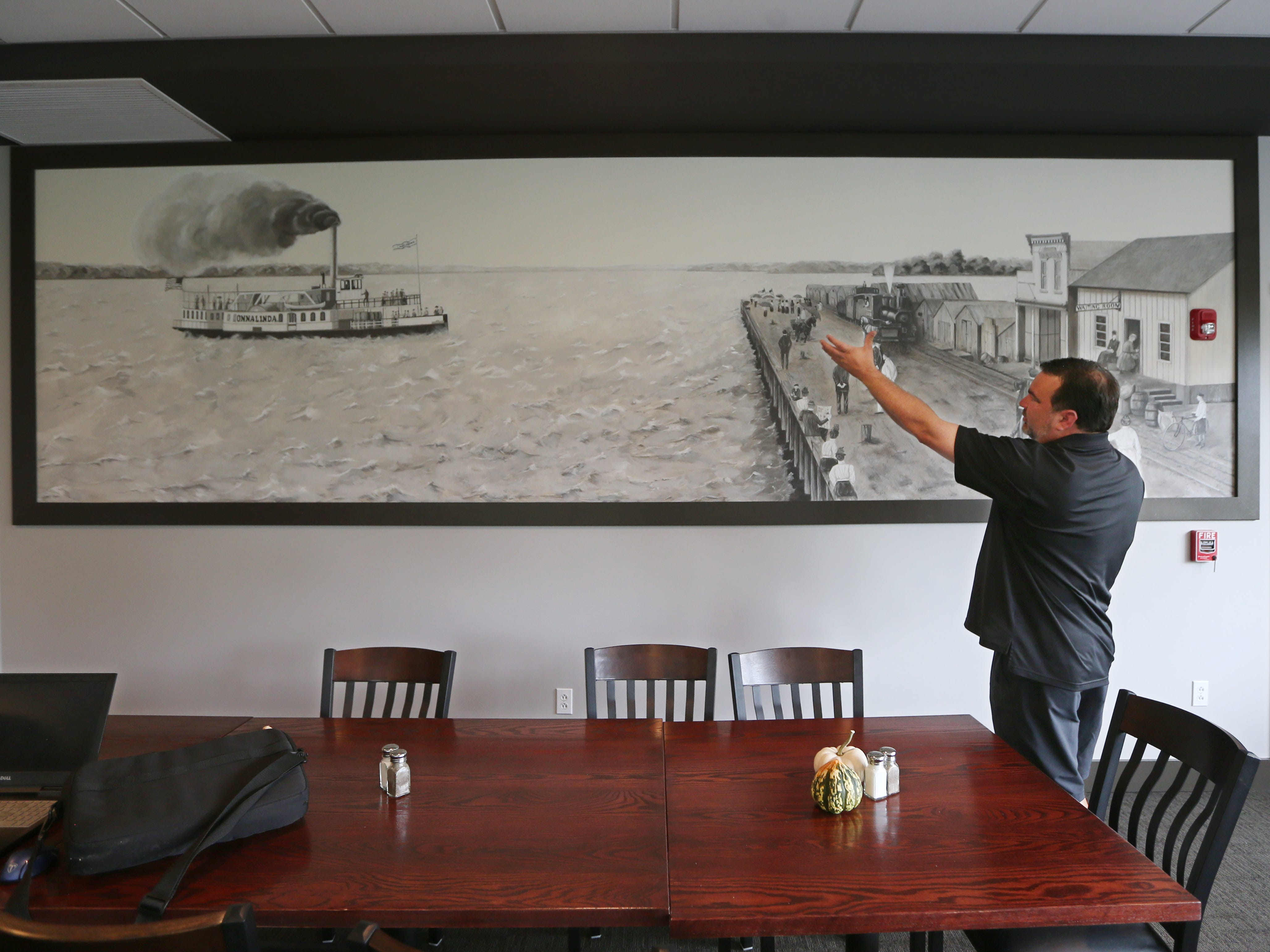 Nick Violas talks about a large mural depicting Canandaigua Lake that hangs in his new party room.
