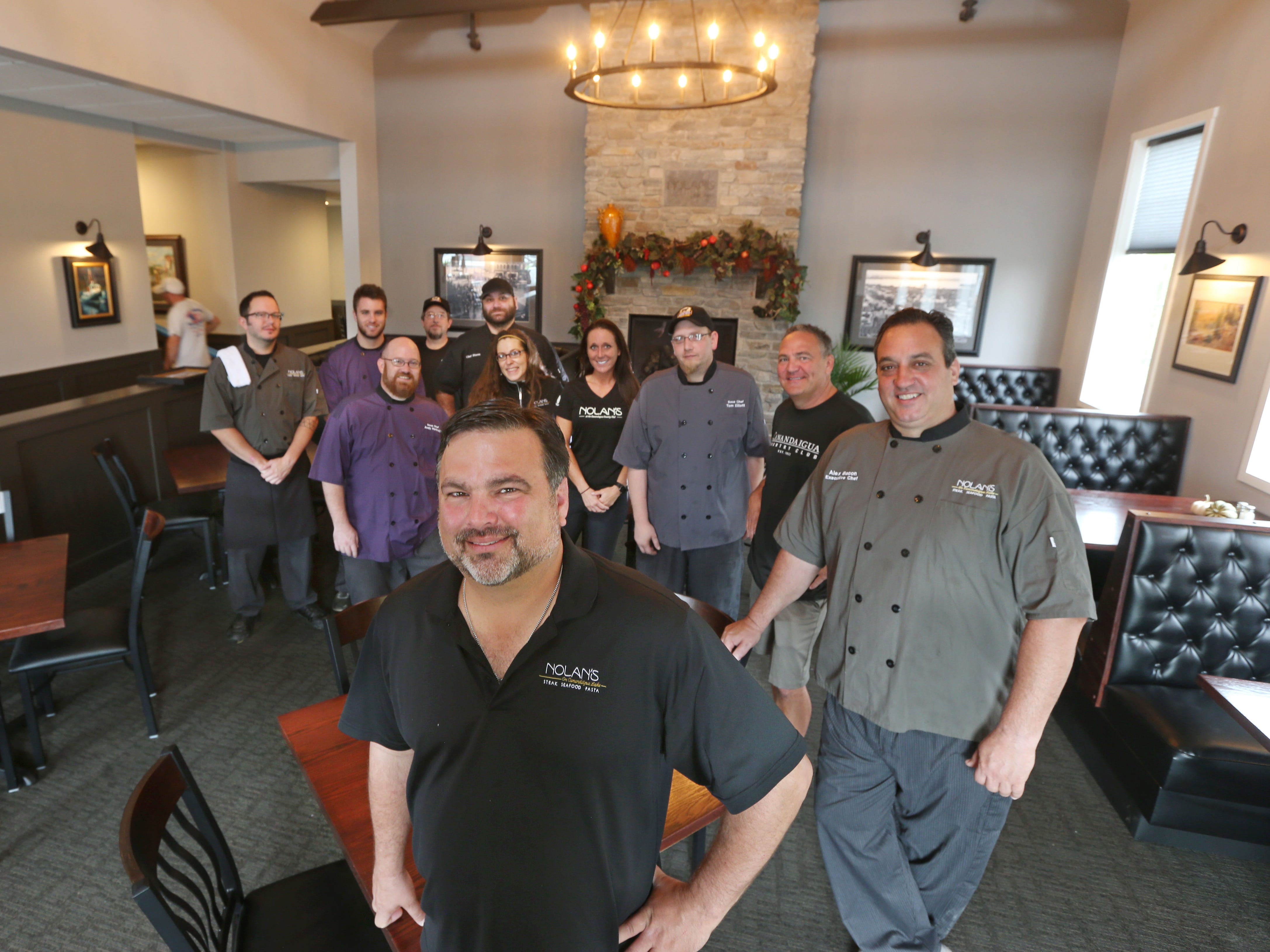 Nick Violas, front center, owner of Nolan's, is surrounded by his restaurant staff, including executive chef Alex Bacon, far right, at Nolan's in Canandaigua Thursday, Oct. 11, 2018.  The popular restaurant, which burned down July 13, 2017, is set to reopen.