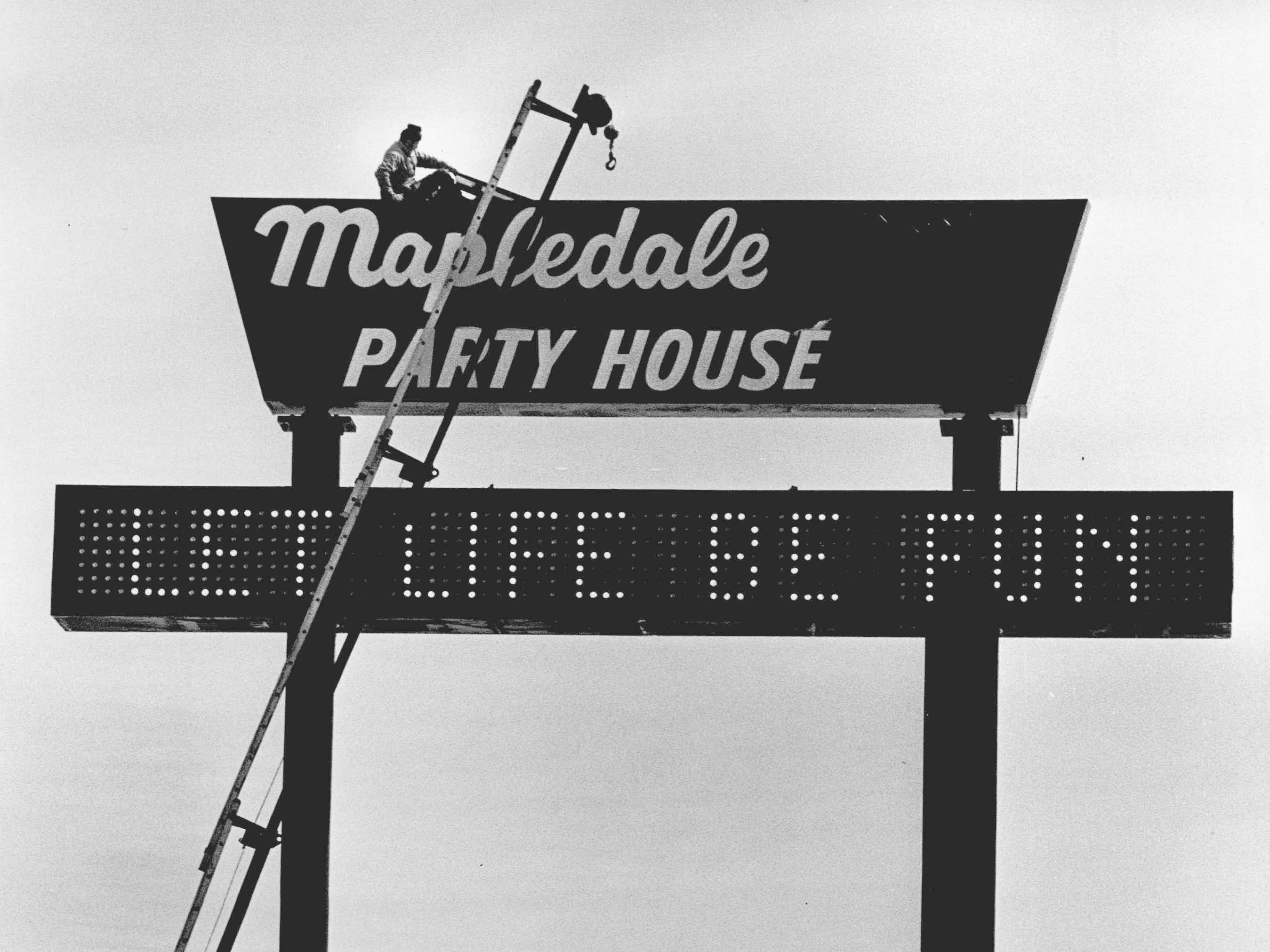 Routine maintenance is being done on sign at Mapledale Party House after a windstorm in 1979.
