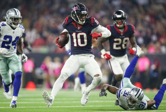 Houston Texans wide receiver DeAndre Hopkins (10) runs with the ball after a reception as Dallas Cowboys cornerback Byron Jones (31) attempts to make a tackle.