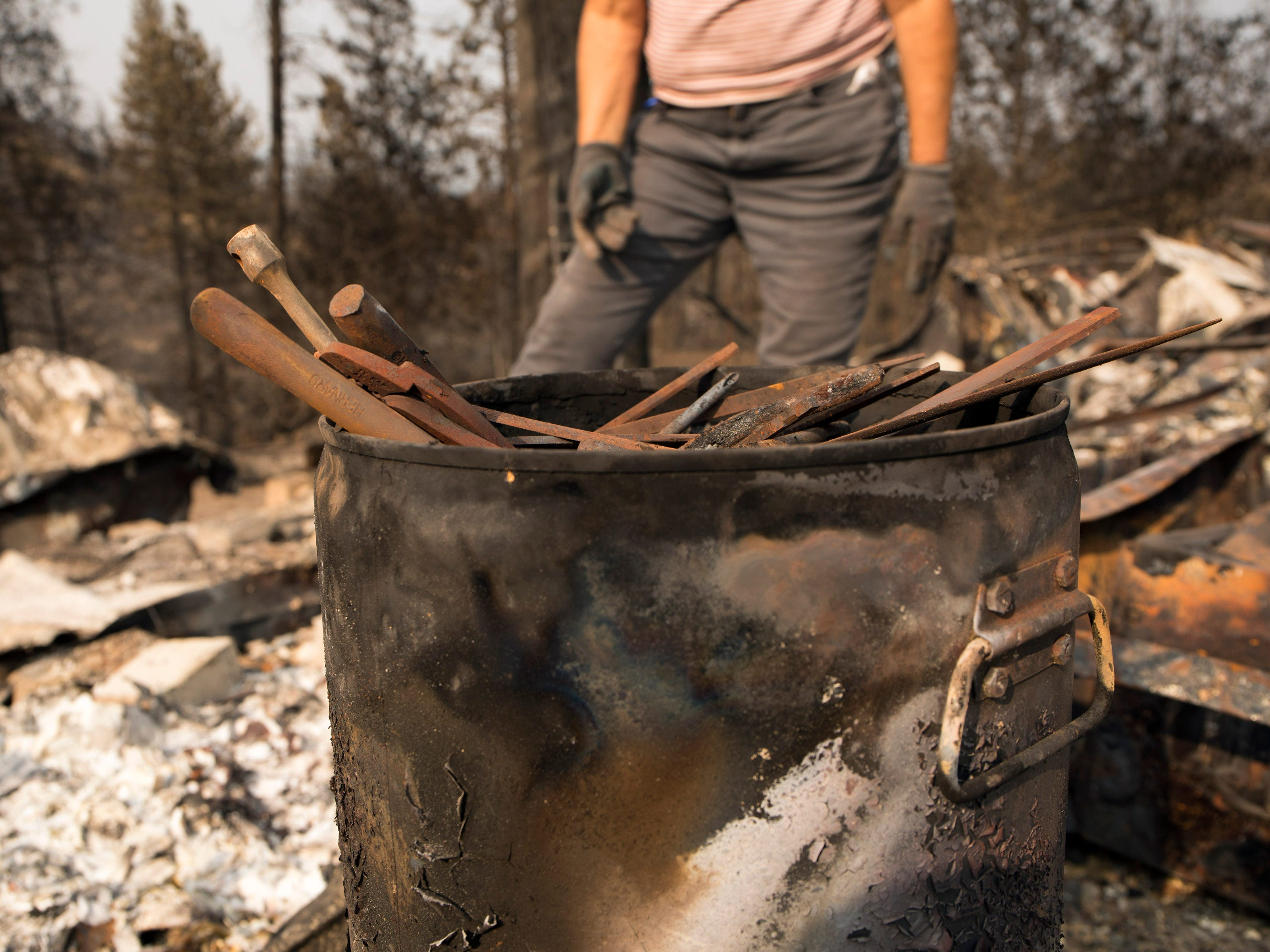 Marci Fernandes, 62 searches the ashes of her home destroyed in the Carr fire for her husband's tools in Keswick, Calif., Saturday, August 26, 2018.  Fernandes lost her husband earlier this year and her mother immediately after the fire.