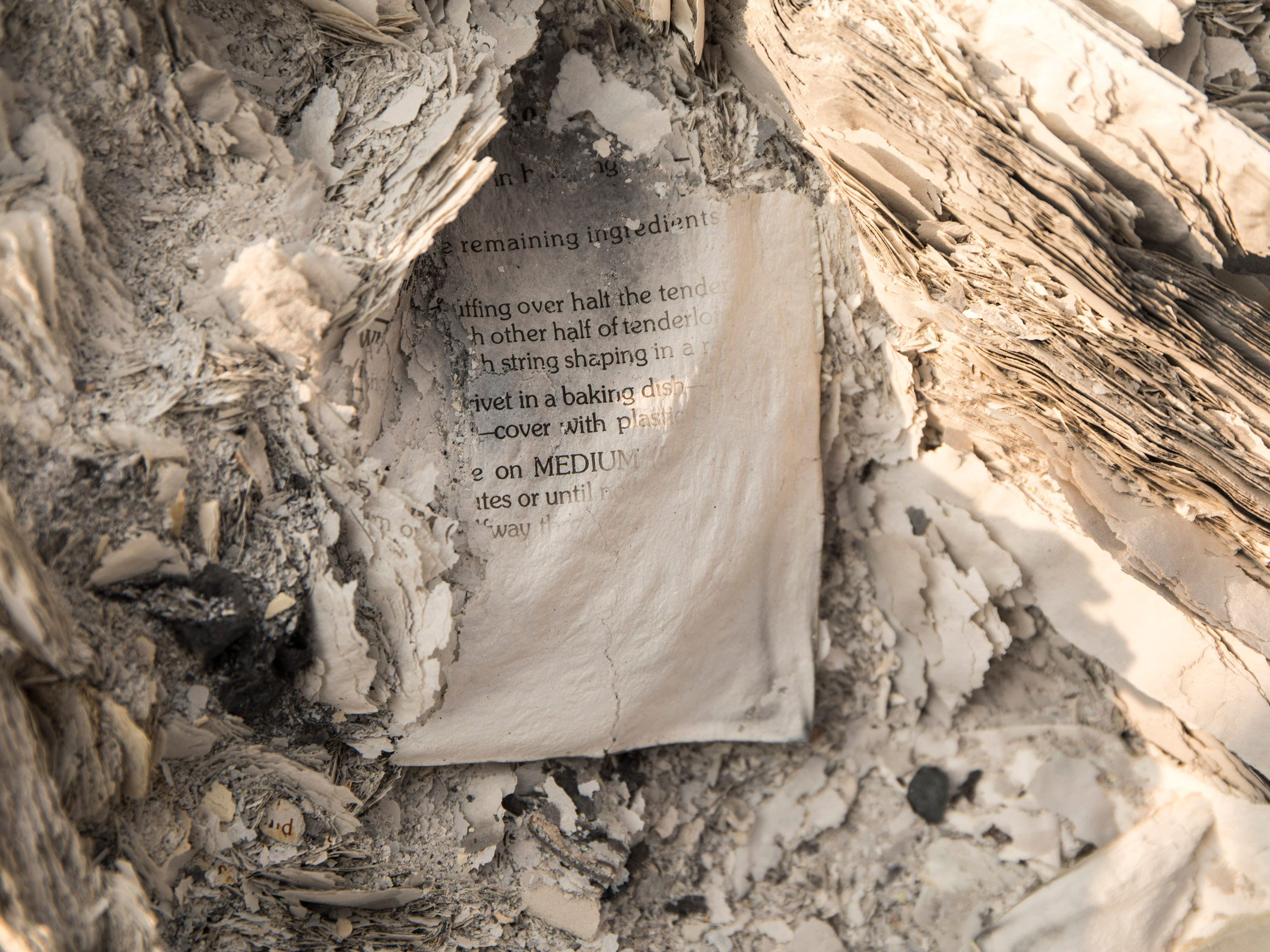 A page from a cookbook lays in the ashes of a home on Keswick Rd. near Tanstaafl Lane lost in the Carr fire in Keswick, Calif., Saturday, August 26, 2018.