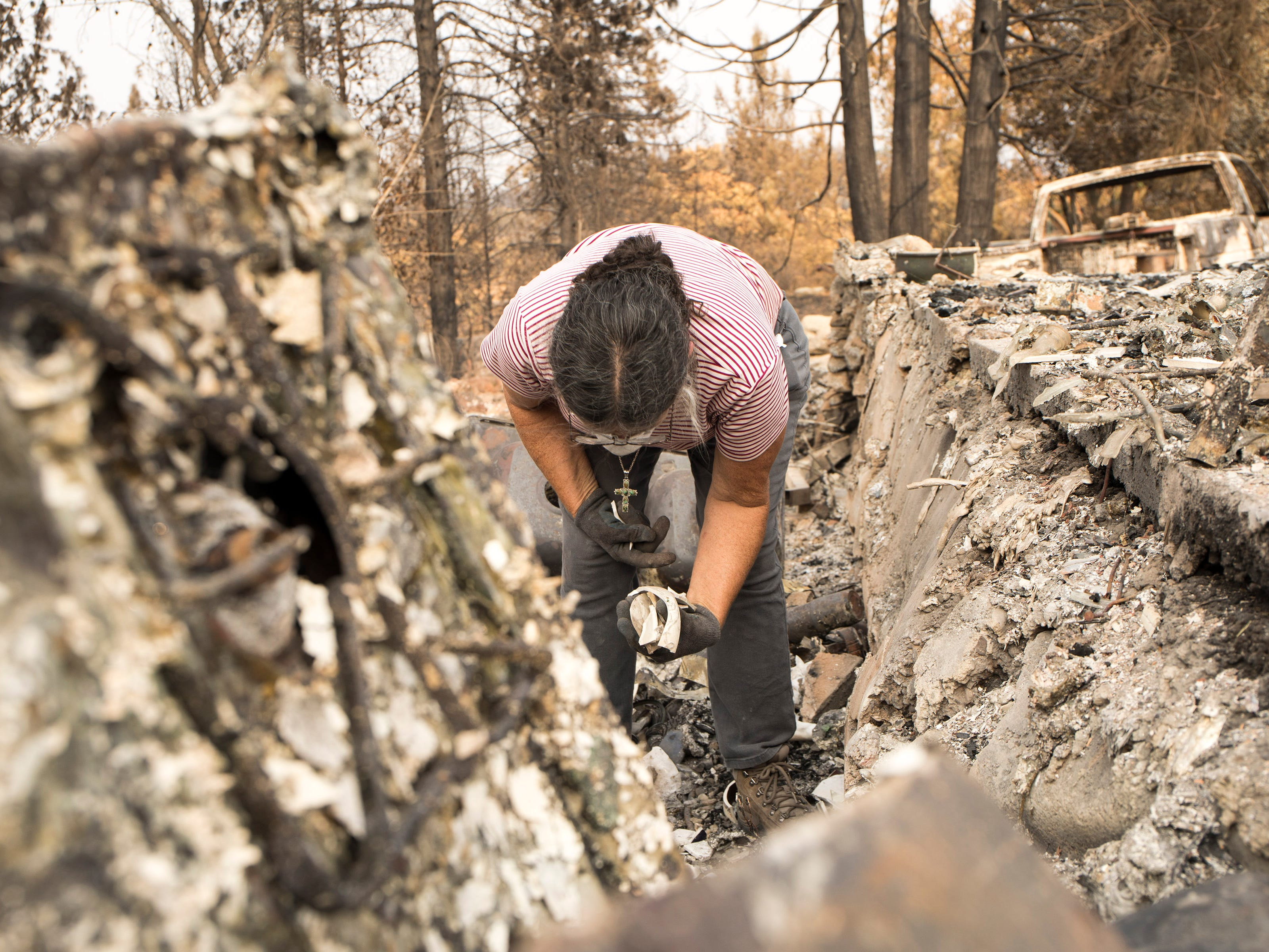 Marci Fernandes, 62 searches through the ashes of her home on Keswick Rd. near Tanstaafl Lane after the Carr fire in Keswick, Calif., Saturday, August 26, 2018.