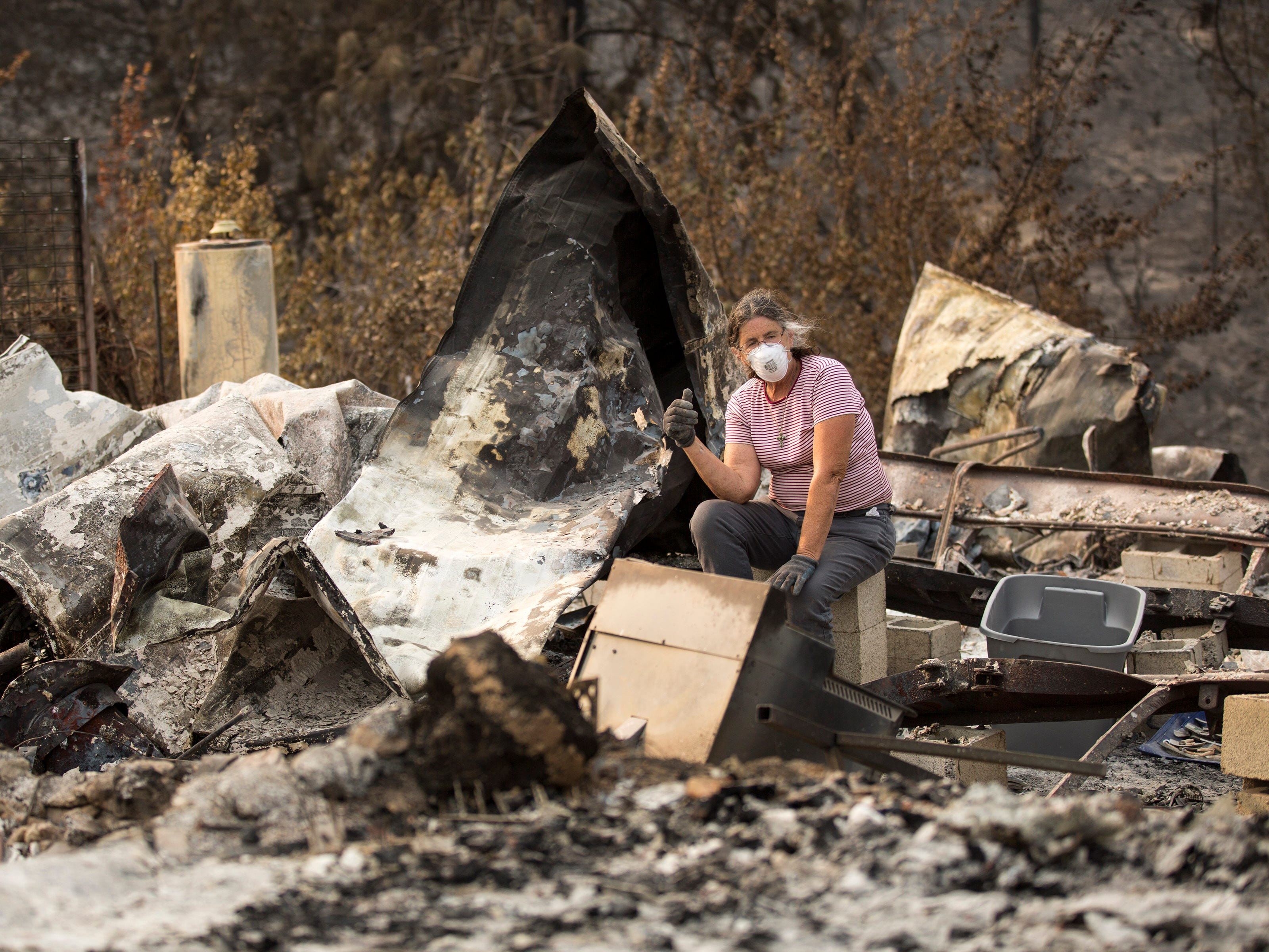 Marci Fernandes, 62 sits among the rubble of her home on Keswick Rd. near Tanstaafl Lane lost to the Carr fire this summer in Keswick, Calif., Saturday, August 26, 2018.