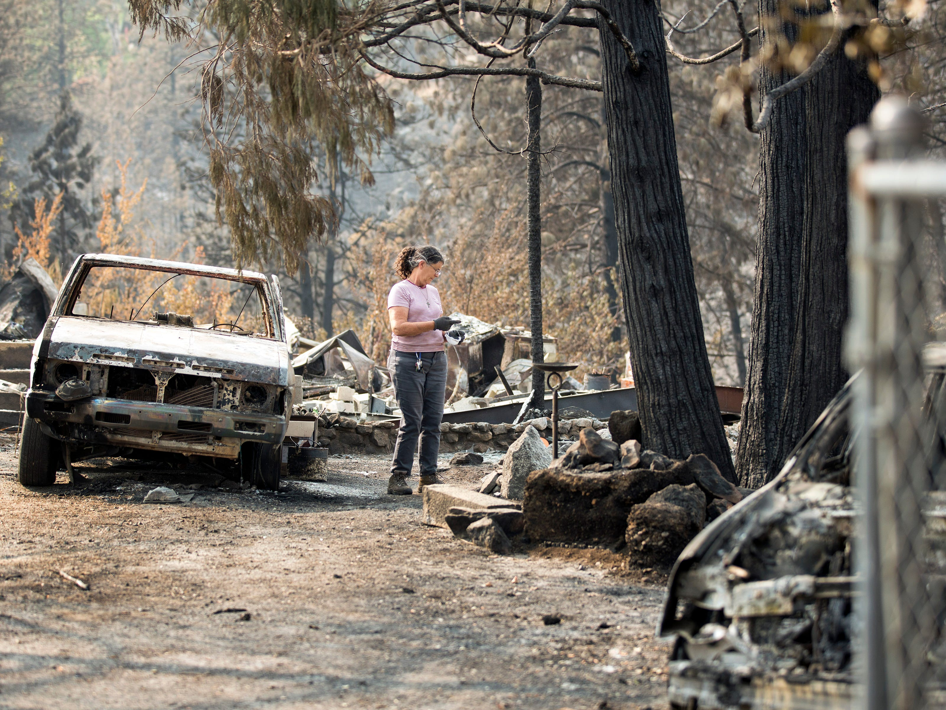 Marci Fernandes, 62 searches the ashes of her home on Keswick Rd. near Tanstaafl Lane lost in the Carr fire in Keswick, Calif., Saturday, August 26, 2018.