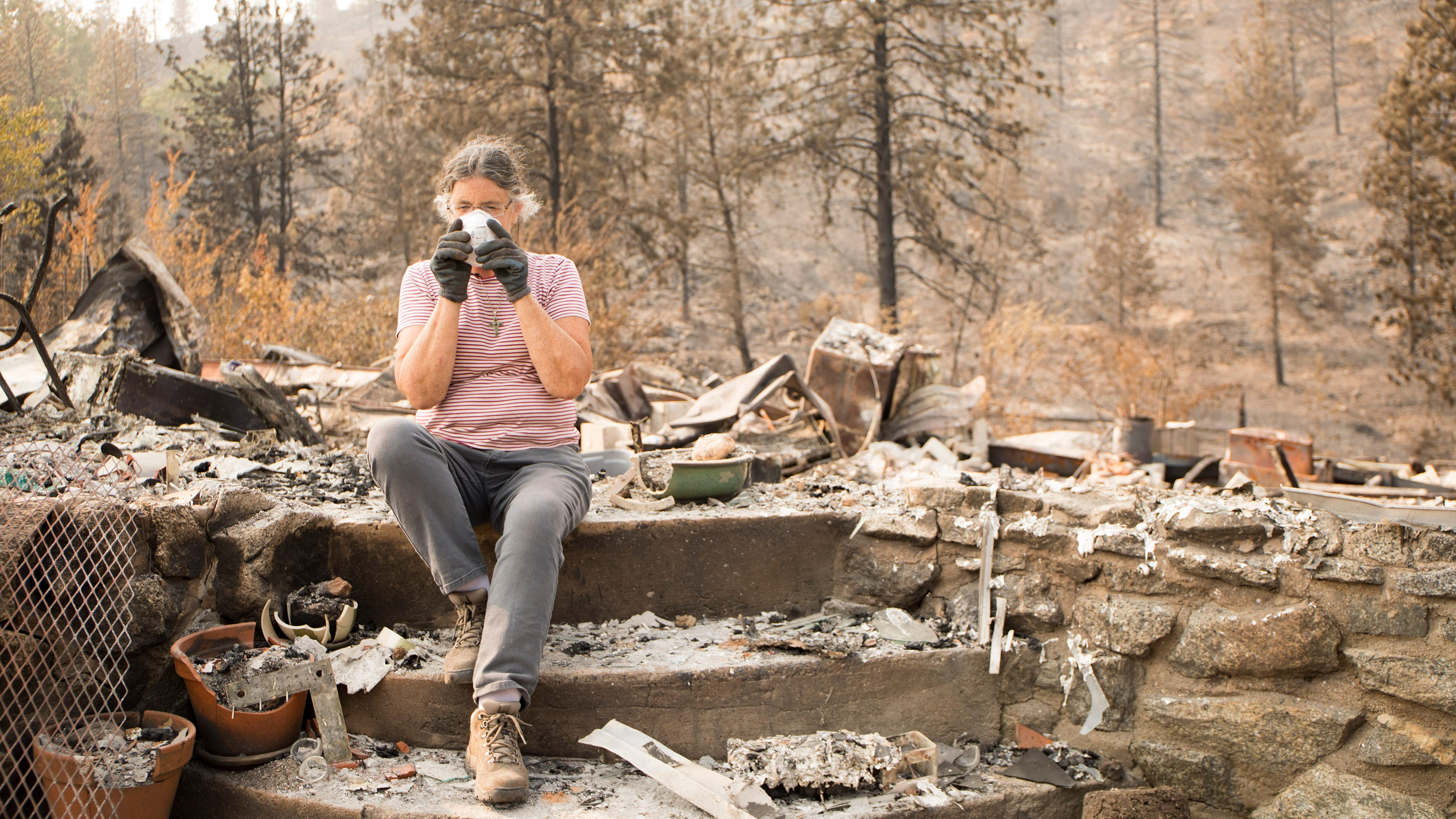 Marci Fernandes, 62 gears up to search through the ashes of  her home on Keswick Rd. near Tanstaafl Lane destroyed in the Carr fire in Keswick, Calif., Saturday, August 26, 2018.