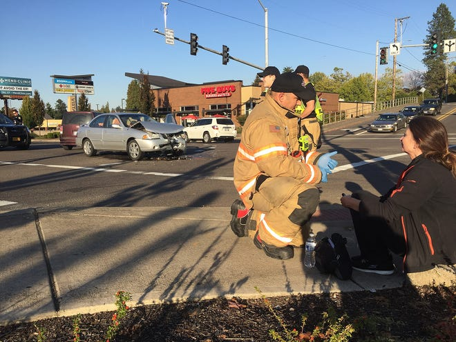 Salem Fire Department firefighter/paramedic Matt Fimbres talks to the driver of a silver Nissan, background, who was involved in a two-car collision at the intersection of Vista Avenue and Commercial Street Wednesday afternoon, October 10, 2018 in Salem, Oregon. The driver of the Nissan was transported to the hospital, the driver and passenger of the other car declined transport.