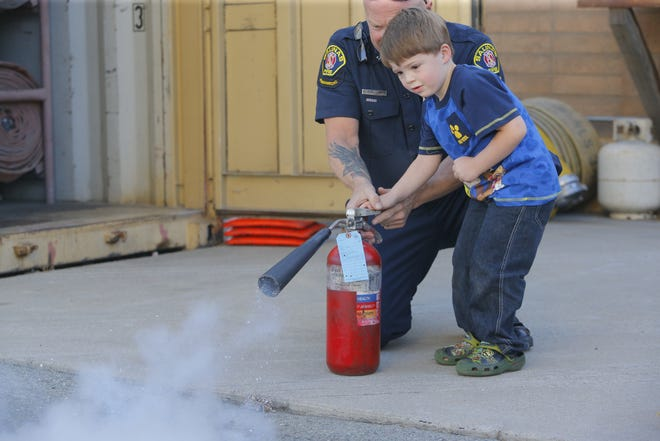 Nathaniel Duncanson, 4, of Salinas, uses a fire extinguisher, with help from Salinas fire Capt. Keith Emery, at the Salinas Fire Department's District 3 station open house Wednesday. The event is part of a weeklong effort to educate people about fire safety.