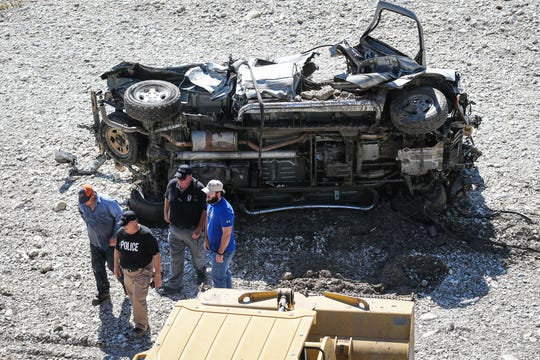 Search and rescue crew investigate for clues in a truck that was buried in the sand after South Llano River flooded Wednesday, Oct. 10, 2018, in Junction.