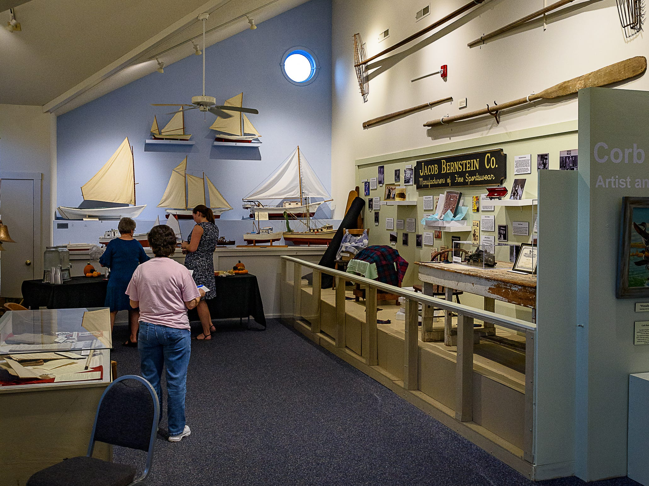 Members of the museum staff prepare for the opening of three exhibitions for fall at the Museum of Chincoteague on Wednesday, Oct. 10.