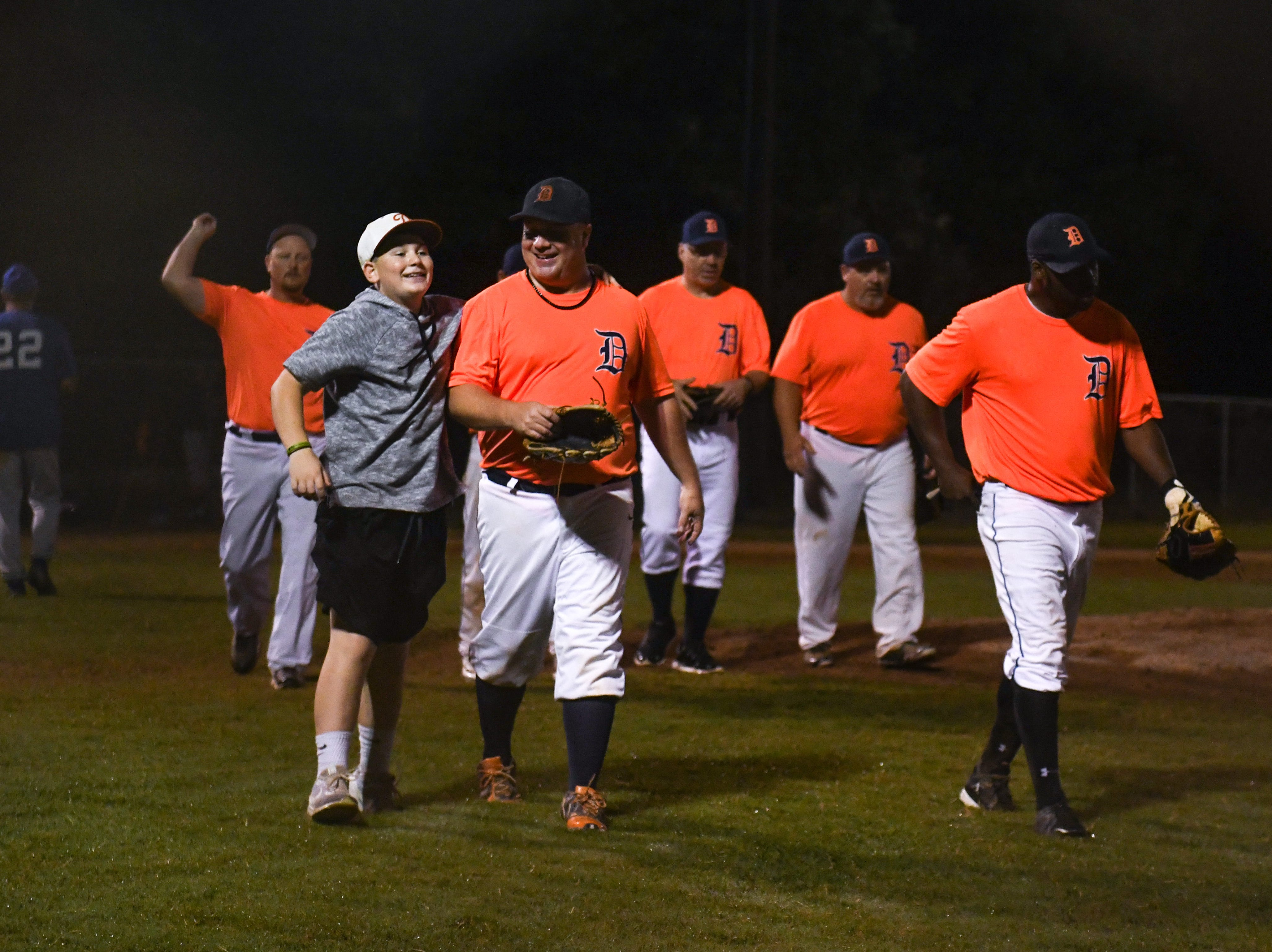 Jerry Pierson and son Tucker Pierson celebrate after winning a game in the new Ty Cobb Senior Baseball League in Salisbury on Tuesday, Oct 9, 2018.