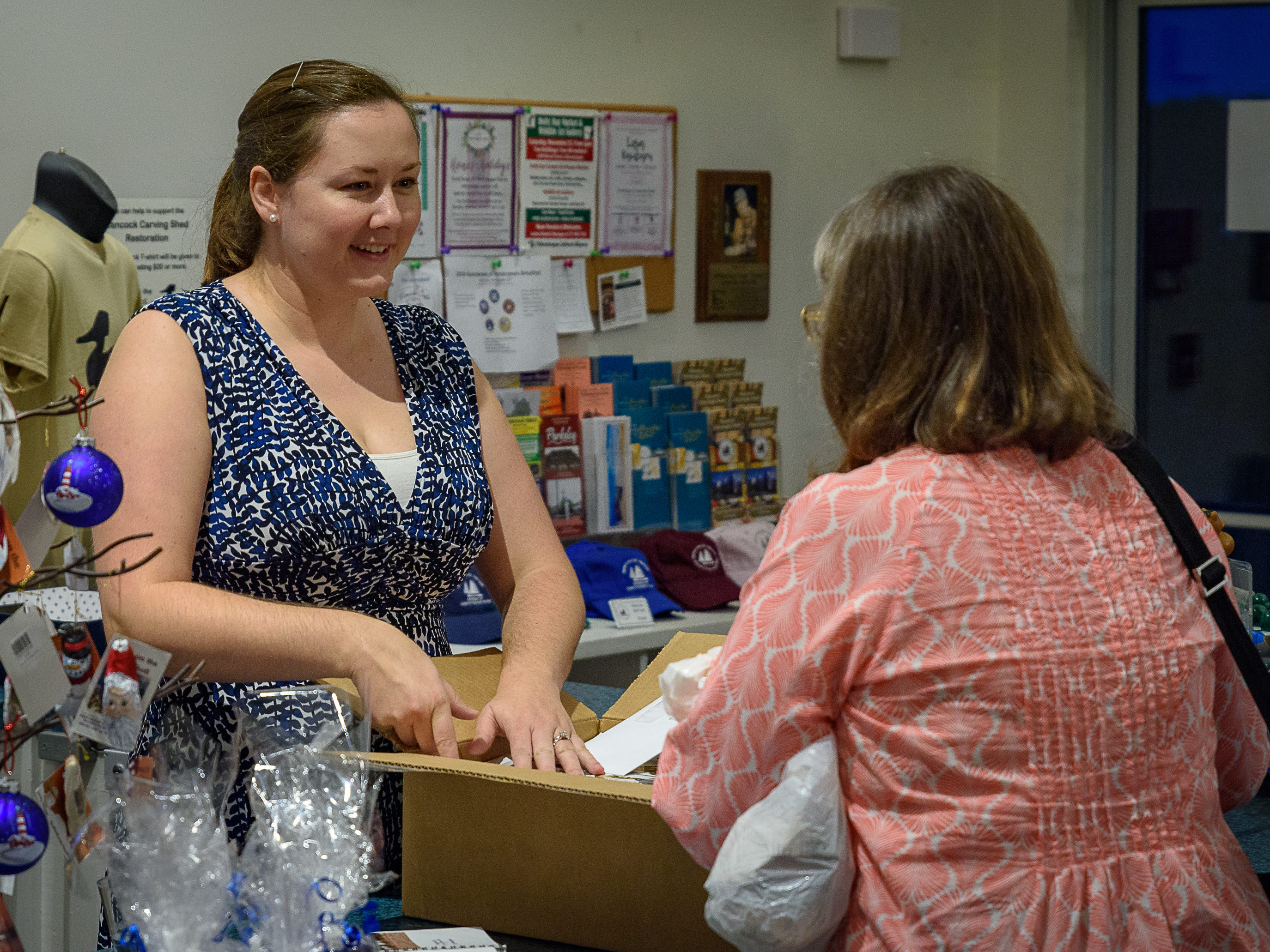 Maria Grenchik, executive director of the Museum of Chincoteague,  goes over some items with a patron at the event.