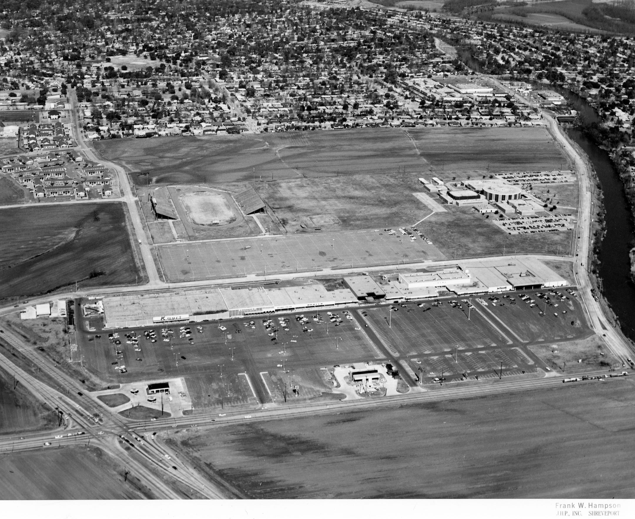 An aerial photograph of the Eastgate Shopping Center and Captain Shreve High School in the late 1970s. The shopping center opened in 1975 with a K-Mart, Kroger, Wilson's, Bealls, Eckerd's and movie theater.