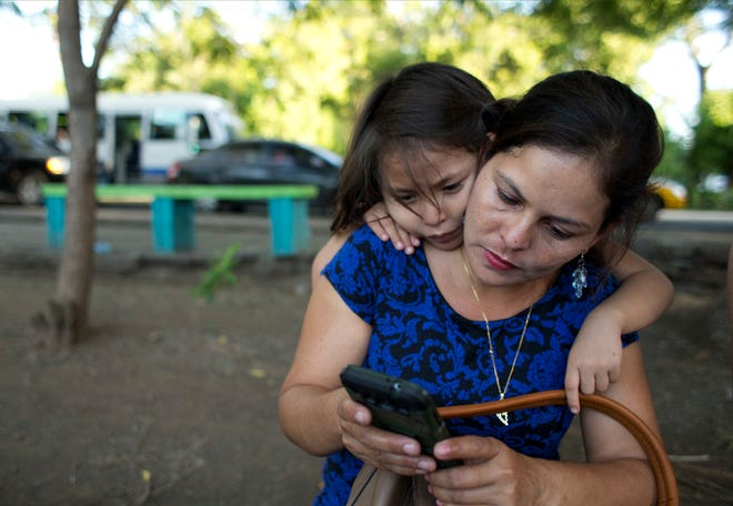 Araceli Ramos, with her five-year-old daughter, Alexa, peering over her shoulder, looks through Facebook pictures posted by Alexa's former foster family in Michigan, during an interview in a park in San Miguel, El Salvador, on Aug. 18, 2018. The Barrs, Kory, a physical therapist at a nearby rehabilitation hospital, and his wife, Sherri, who ran a home-organization business, had three daughters who were raised in a devout home and already had fostered two Salvadoran sisters in 2013. (AP Photo/Rebecca Blackwell)