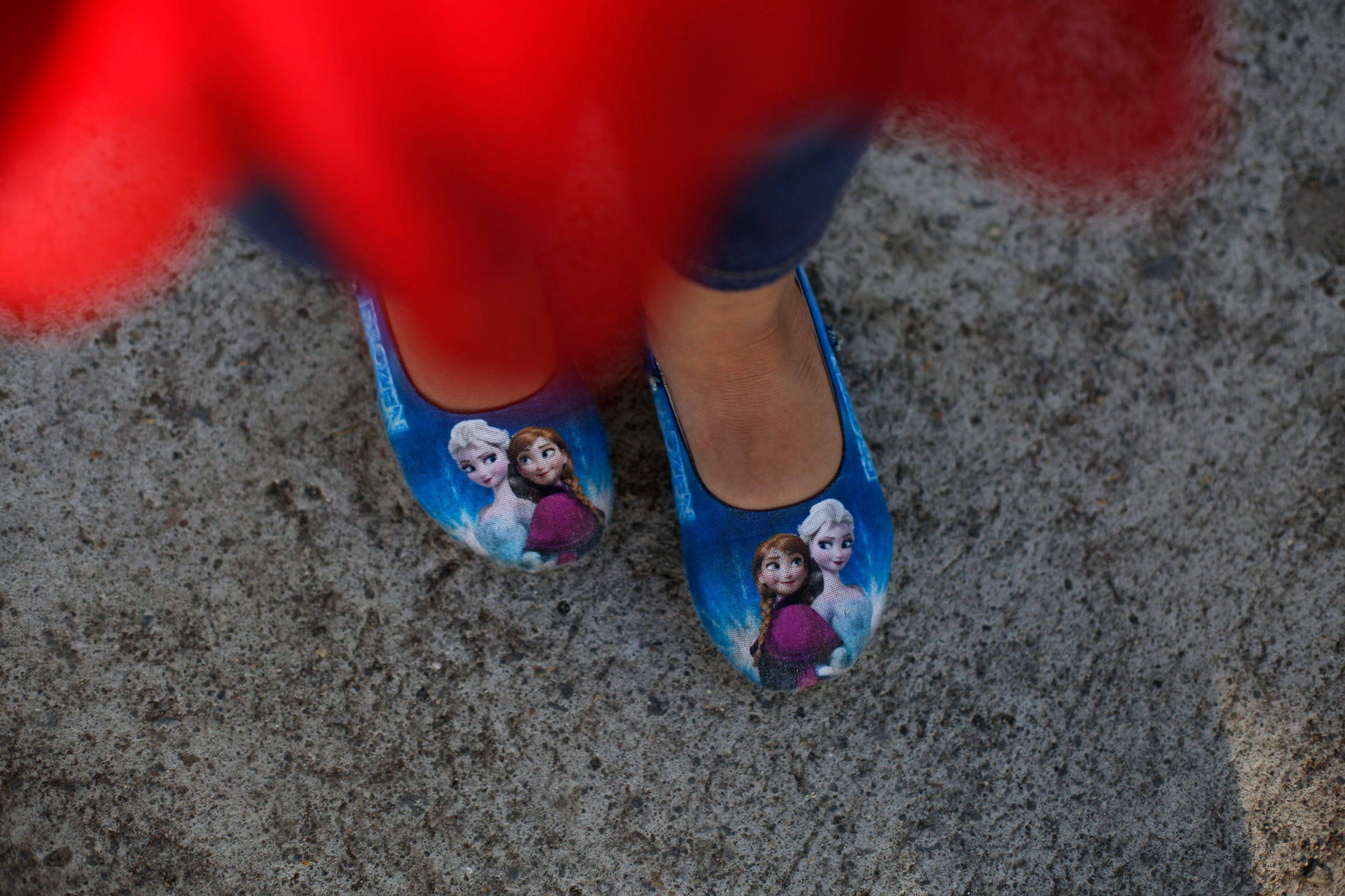 "Five-year-old Alexa wears shoes depicting characters from Disney's ""Frozen"" movie as she and her mother Araceli Ramos meet with Associated Press journalists in a park in San Miguel, El Salvador, on Aug. 18, 2018. (AP Photo/Rebecca Blackwell)"