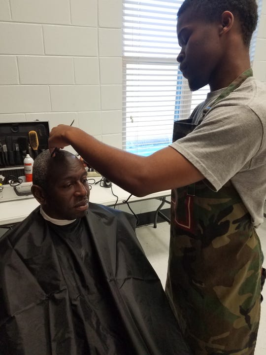 Rod Williams is the custodian of Walker-Ford Community Center, here being trimmed by Derrick Pete. Williams has come to the center each week for a year and a half.