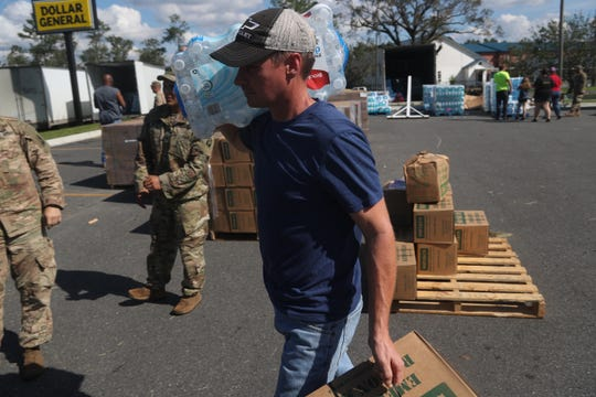 Benjamin O'Neal gets one case of food and one case of water National Guardsmen hand out supplies to Liberty County at Dollar General in Hosford after Hurricane Michael Thursday, Oct. 11, 2018.