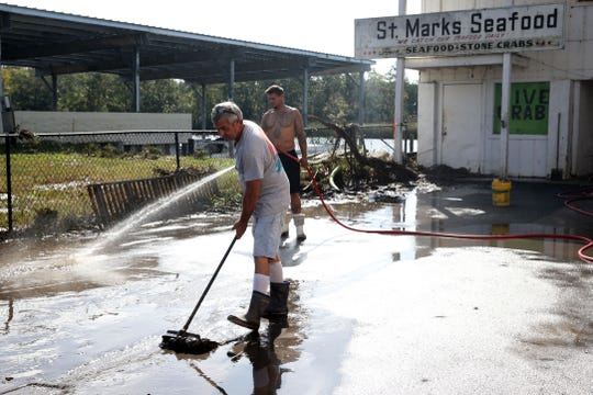 St. Marks Seafood employees work to remove sludge that blankets the ground after Hurricane Michael tears through the Panhandle in St. Marks, Fla. on Thursday, Oct. 11, 2018,