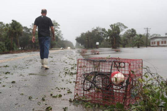 An oyster basket sits in flood waters on the side of U.S. Highway 98 in Apalachicola, Fla. as Steve Nash walks back to his vehicle. Nash's business, Two Mile Seafood, was destroyed by Hurricane Michael Wednesday, Oct. 10, 2018.