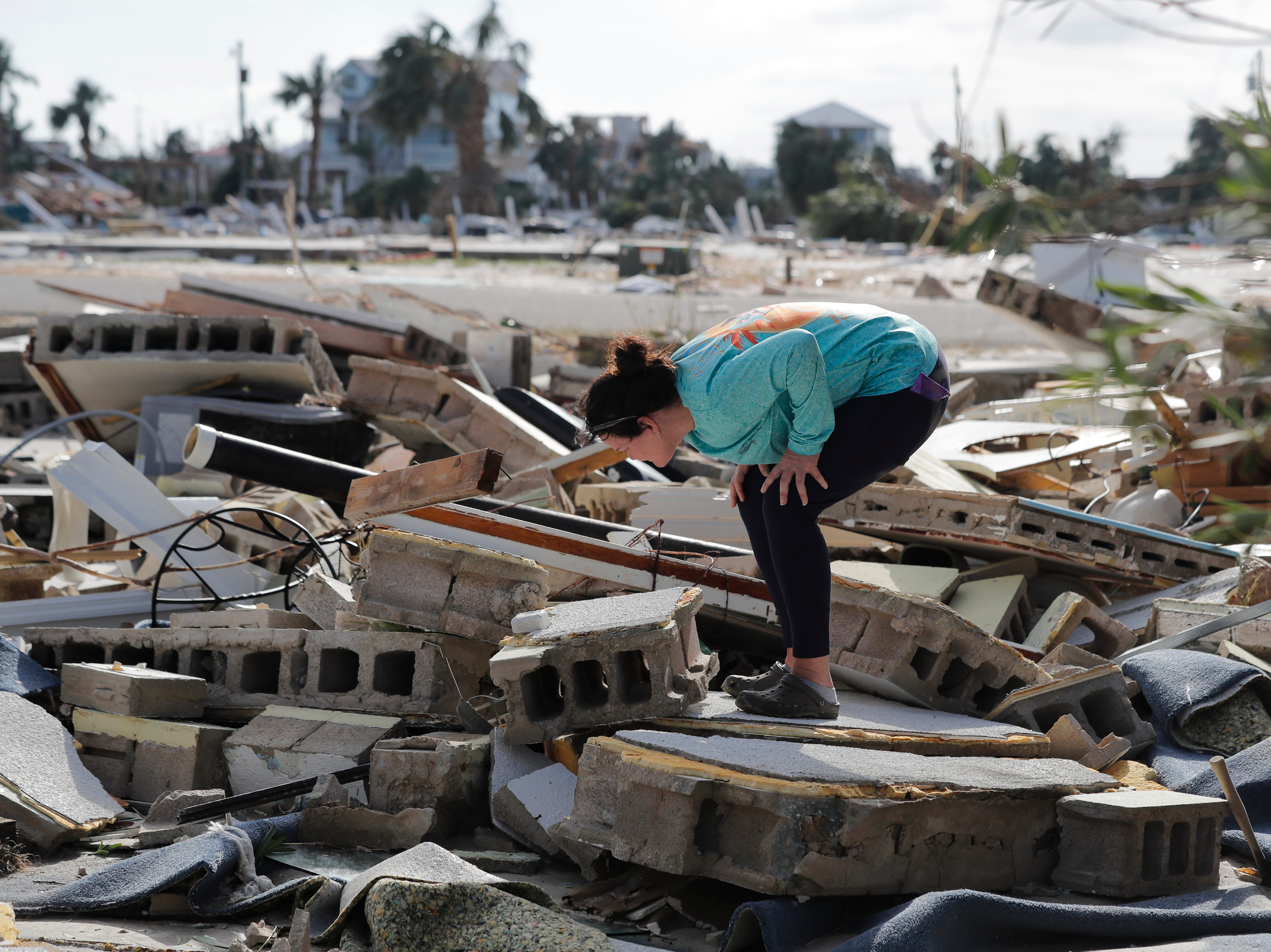 Mishelle McPherson looks for her friend in the rubble of her home, since she knows she stayed behind in the home during Hurricane Michael, in Mexico Beach, Fla., Thursday, Oct. 11, 2018. (AP Photo/Gerald Herbert)