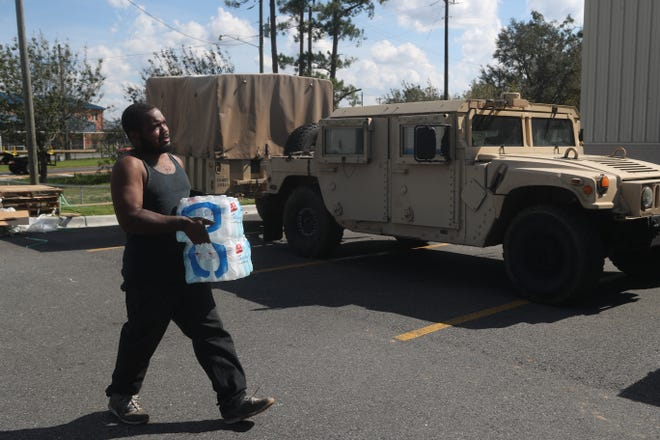 Joseph Jones gets two cases of bottled water as National Guardsmen supply food and water to Liberty County at Dollar General in Hosford after Hurricane Michael Thursday, Oct. 11, 2018.